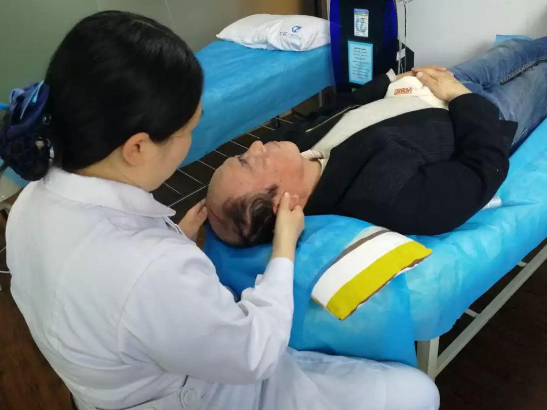 """护士为彭爷爷进行""""调穴通经活络""""疗法治疗"""